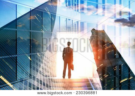 Back View Of Young Businessman Standing On Abstract City Background. Success And Access Concept. Dou