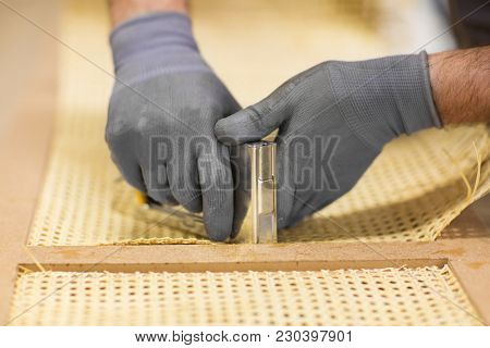 production, manufacture and industry concept - assembler with staple gun making furniture