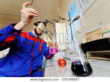 A Young Scientist Conducts Chemical Experiments In The Laboratory