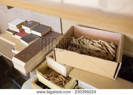 furniture production, manufacture and woodworking industry concept - wood dowel pins and board samples at workshop