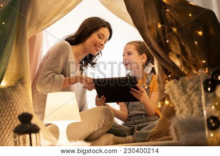 family, hygge and technology concept - happy mother and little daughter with tablet pc computer in kids tent at night at home
