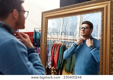 shopping, fashion and sale concept - man or hipster choosing clothes and looking at mirror at vintage clothing store