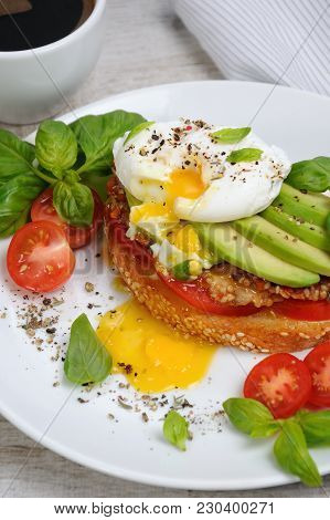 Egg Poached On A Toasted Slice Of Baguette With Tomato, Spicy Ham And Avocado, Sprinkled   Spices An