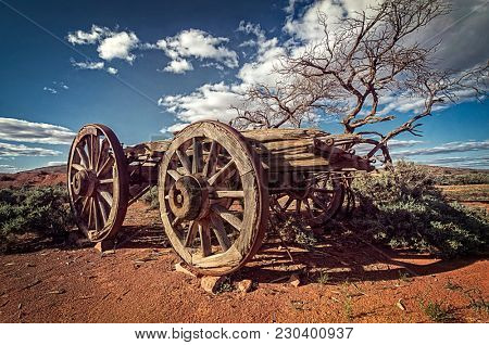 Australian Outback savanna with an old vintage derelict horse-drawn carriage at the bush under blue sky