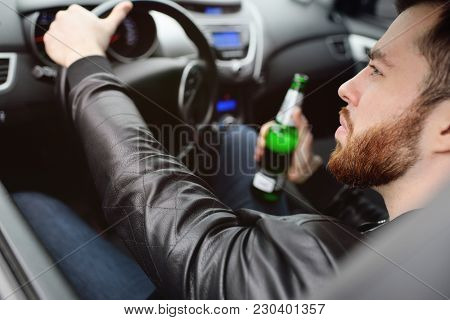 A Young Handsome Bearded Man With A Bottle Of Beer Or A Low-alcohol Drink At The Wheel Of A Car. Dri