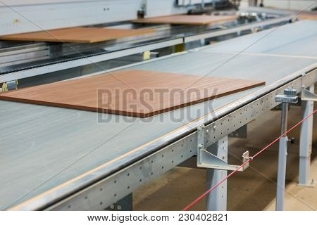 production, manufacture and woodworking industry concept - wooden boards processing on conveyer at furniture factory workshop