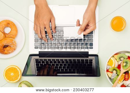 Healthy Business Lunch In Office, Fruit Salad Bowl Near Laptop On White Background. Organic Meal And