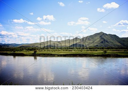 Siberia, Russia During The Summer Time From A Moving Train.  Mountain View Behind A Tranquil Lake.