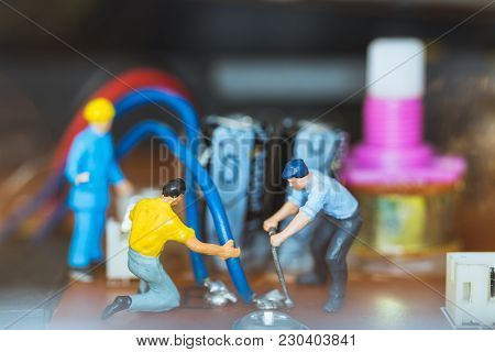 Miniature People : Worker Team Repairing Electronic Circuits.