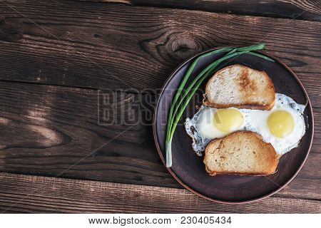 Scrambled Eggs On A Plate. A Plate Of Scrambled Eggs, Toasted Bread And Onions Placed On A Wooden Su