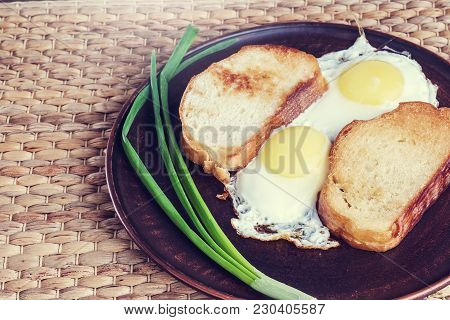 A Scrambled Eggs On A Brown Plate. Plate With Scrambled Eggs, Toasted Bread And Onions Is On The Fab