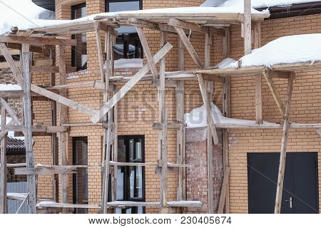 Facade Of The House Under Construction. Brick House Building In The Winter Using The Wood Add-ons, S