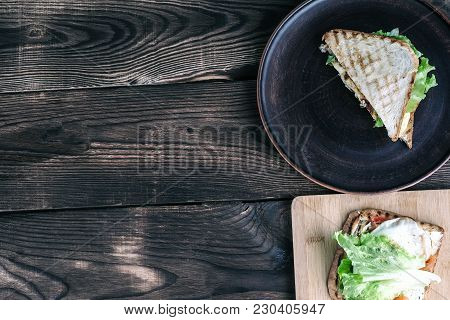Two Sandwiches On Plates On A Wooden Surface. One Sandwich And Tomatoes With Onions On A Wooden Plat