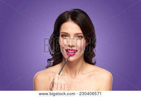 beauty, cosmetics and people concept - beautiful young woman with make up brush applying berry lipstick over ultra violet background