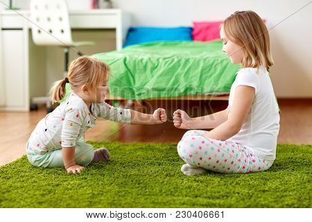 childhood, leisure and family concept - happy little girls playing rock-paper-scissors game or making fist bump at home