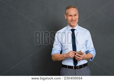 Relaxed senior business man in formal typing message on smartphone isolated on gray background. Portrait of a happy mature businessman using cell phone. Satisfied leader checking mail with copy space.