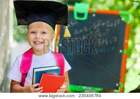 Happy Girl With Books  In Graduation Cap
