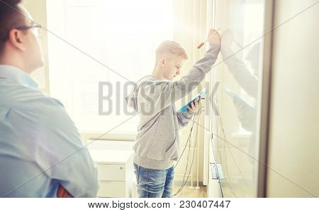 education, school, learning and people concept - student boy writing something on blank white board and teacher in classroom