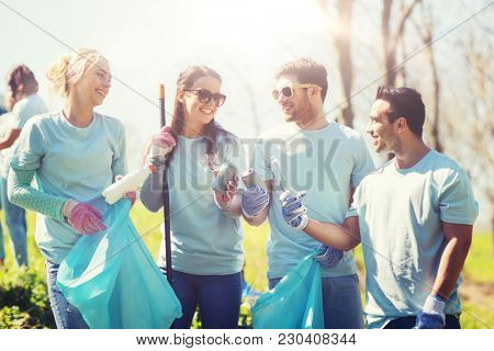 volunteering, charity, cleaning, people and ecology concept - group of happy volunteers with garbage bags cleaning park area from old cans and bottles