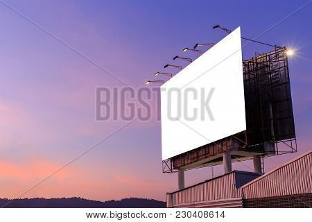 Large White Advertising Billboard On Top Of The Building And Sky Background In Sunset Time. For Desi
