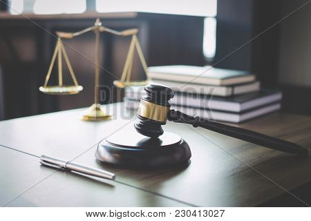 Scales Of Justice And Gavel On Wooden Table And Lawyer Or Judge Working With Agreement In Courtroom,