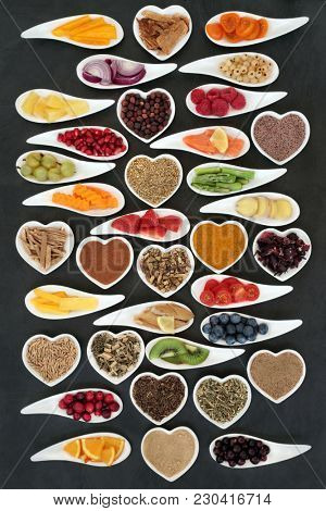 Super food nutrition for a healthy heart concept with fresh vegetables, fruit, fish, supplement powders and medicinal herbs. Foods very high in antioxidants, omega 3 fatty acids, fibre, anthocyanins,