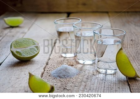 Alcohol Shot Drink. Silver Tequila With Lime And Salt On The Wooden Table.