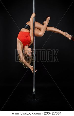 Beautiful Young Woman Pole Dancer In Red Top On Pylon. Studio Shot On Black Background. Copy Space.