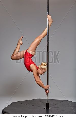 Beautiful Young Woman Pole Dancer In Red Bodywear On Pylon. Studio Shot On Grey Background. Copy Spa
