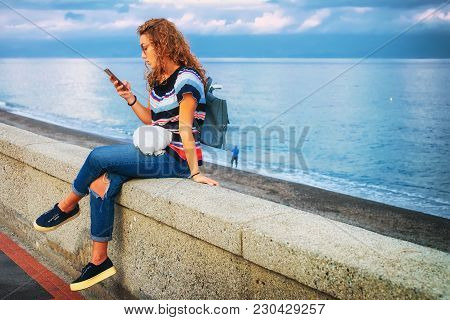 Santa Teresa Di Riva, Italy - September 24, 2017: Young Girl Reading At His Mobile Phone At The Medi