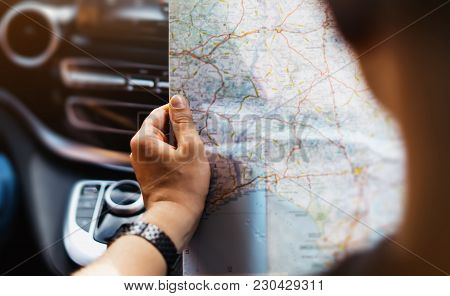 Hipster Man Holding In Male Hands And Looking On Navigation Map In Auto, Tourist Traveler Hiker Driv