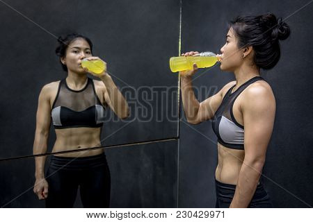 Young Asian Athlete Woman Drinking Sport Drink Or Energy Drink After Exercise In Fitness Gym, Health