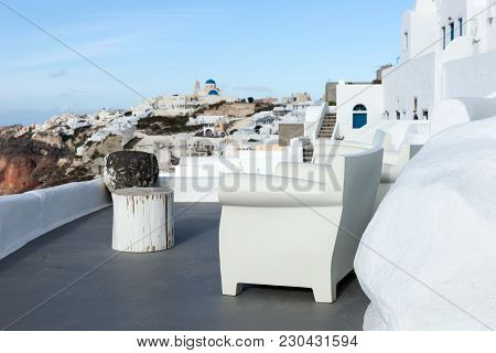 White Terrace With Armchair And View Of Oia Town In Santorini