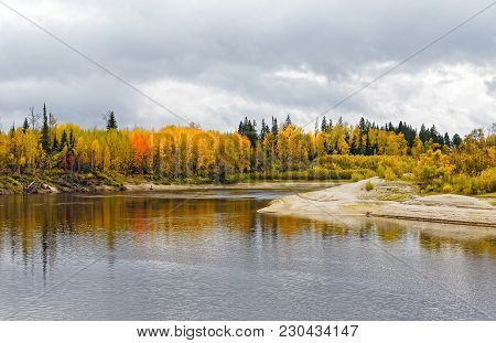 Trees Painted With Autumn Cooling On The Bank Of The Wild Taiga River. The Natural Beauty Of Nature