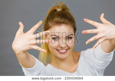 Happy Proud Young Woman Showing Her Hands In Front Of Her Face, Studio Shot Grey Background.