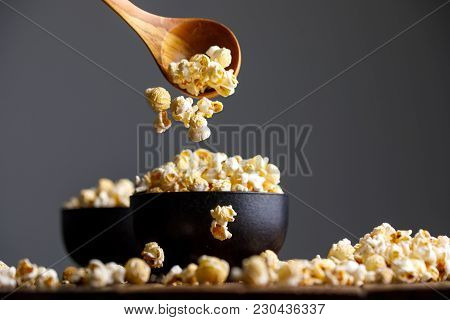 Popcorn Falls From A Wooden Spoon Into Bowls And Around Them.
