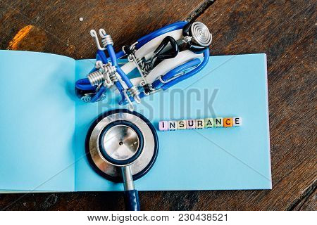 Conceptual Image With Insurance Word Block On Note Pad.handcrafted Toy And Used Stethoscope. Soft Fo