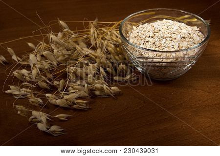 Oat Ears Stems And Oat Flakes In A Bowl On A Dark Brown Wood Background. Oat Flakes Small Size Grind