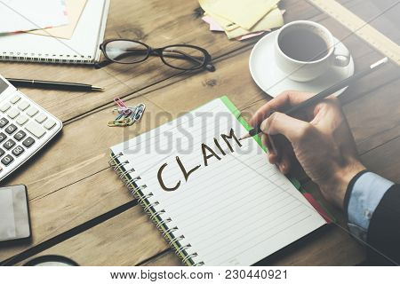 Man Written Claim Text On Notebook Page With Stationary And Coffee On Wooden  Table