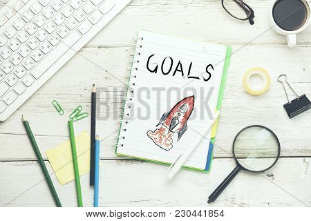 Goals Text On Notebook With Keyboard And Stationary On Table