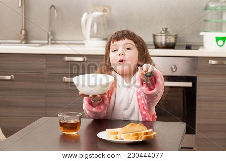 Girl In The Kitchen At The Table. Childhood.
