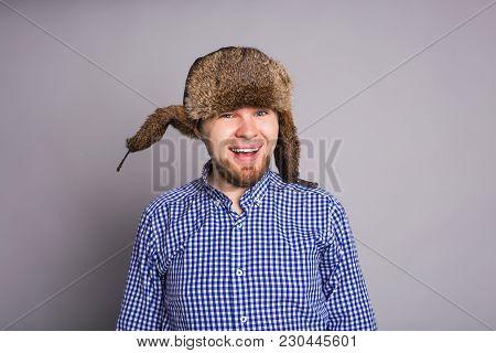 Happy Handsome Young Man In Cap With Earflaps Smiles In Studio.