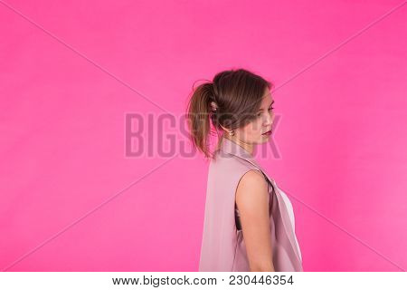 Pretty Stylish Girl With Long Hair Posing Against Pink Background. Fashion Portrait Of Young Happy S