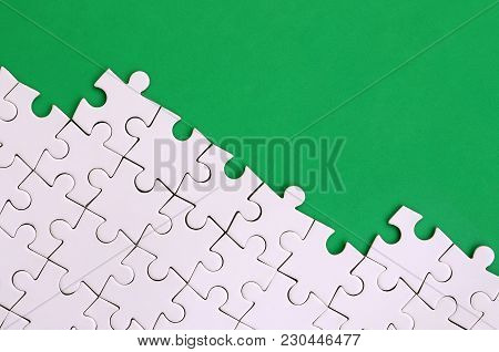 Fragment Of A Folded White Jigsaw Puzzle On The Background Of A Green Plastic Surface. Texture Photo