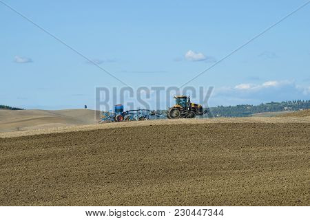 Tuscany, Italy - September 21, 2017: Crawler Tractor With Planter Works In The Field Of Solar Septem