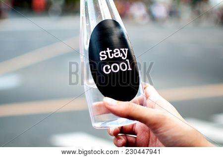 A Woman Is Holding A Platic Bottle With Water Outdoor With Stay Cool Message On It