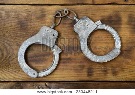 Old And Rusty Police Handcuffs Lie On A Scratched Wooden Surface. The Concept Of An Old Crime