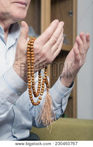 Praying Hands Of An Old Man Holding Rosary Beads