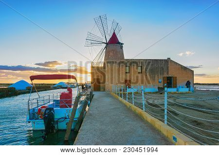 Marsala, Italy - September 19, 2017: Sunset At Windmill And The Salt Evoporation Pond In Marsala, Si