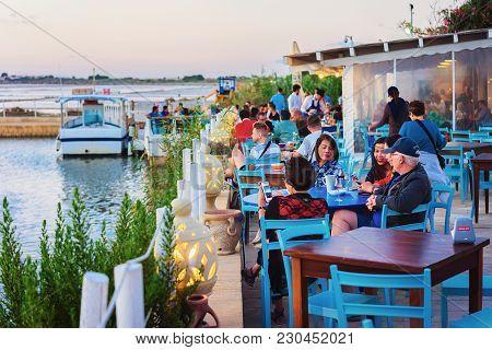 Marsala, Italy - September 19, 2017: People In Street Cafe At The Salt Evaporation Pond In Marsala,
